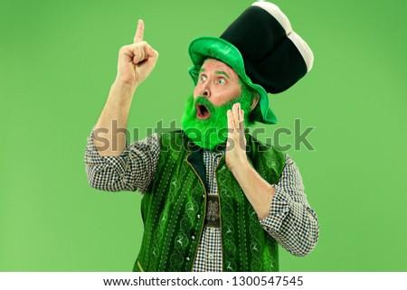 A smiling surprised happy senior man in a leprechaun hat with beard at green studio. He celebrates St. Patrick's Day. The celebration, festive, beer, holiday, alcohol, party, human emotions concept #1300547545