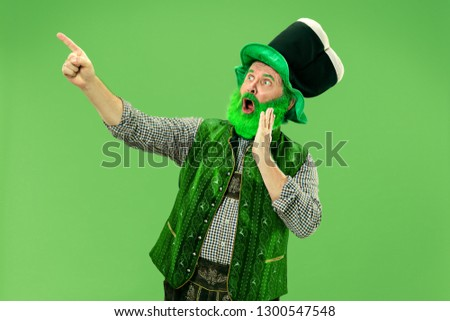 A smiling surprised happy senior man in a leprechaun hat with beard at green studio. He celebrates St. Patrick's Day. The celebration, festive, beer, holiday, alcohol, party, human emotions concept #1300547548