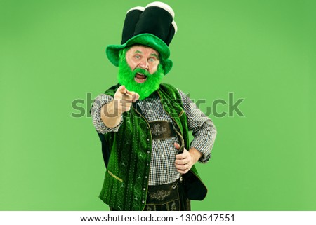 A smiling surprised happy senior man in a leprechaun hat with beard at green studio. He celebrates St. Patrick's Day. The celebration, festive, beer, holiday, alcohol, party, human emotions concept #1300547551