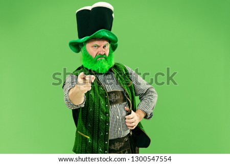 A smiling surprised happy senior man in a leprechaun hat with beard at green studio. He celebrates St. Patrick's Day. The celebration, festive, beer, holiday, alcohol, party, human emotions concept #1300547554