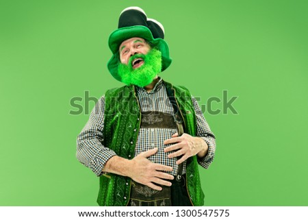 A smiling surprised happy senior man in a leprechaun hat with beard at green studio. He celebrates St. Patrick's Day. The celebration, festive, beer, holiday, alcohol, party, human emotions concept #1300547575