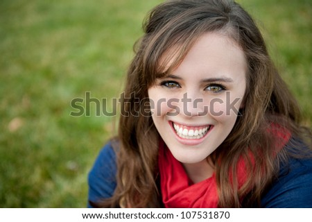 A smiling teenage girl outside on the grass