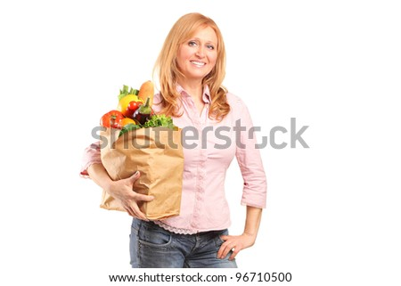 A smiling woman holding a paper bag full of groceries isolated on white background