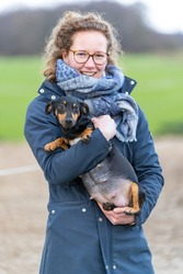 A smiling woman holds a pregnant Jack russel terier in her arms. The dog's big belly can be seen clearly. Outside in the winter. Selective focus on dog