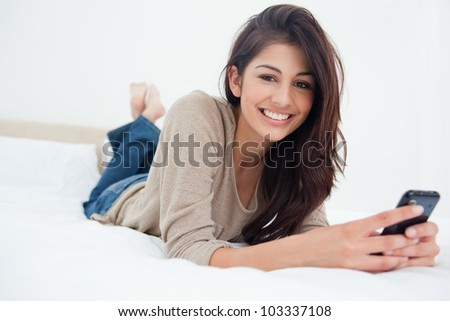 A smiling woman holds her phone in front of her as she looks forward while on the bed.