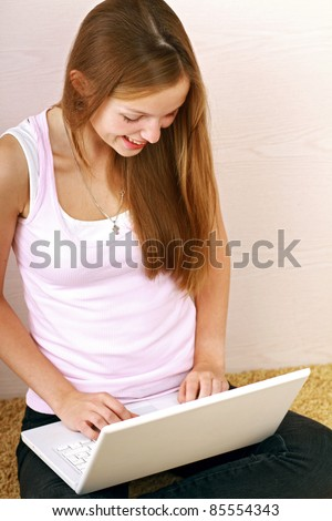 A smiling woman is working with a laptop