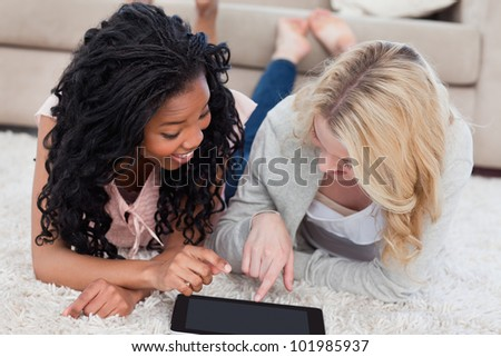A smiling woman lying next to her smiling friend is pointing at a tablet