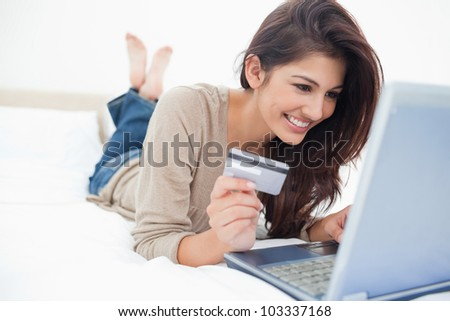 A smiling woman on her bed with laptop in front of her and credit card in hand, with crossed feet.