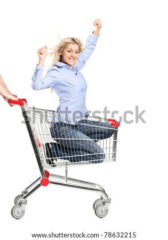 A smiling woman riding in a shopping cart isolated on white background