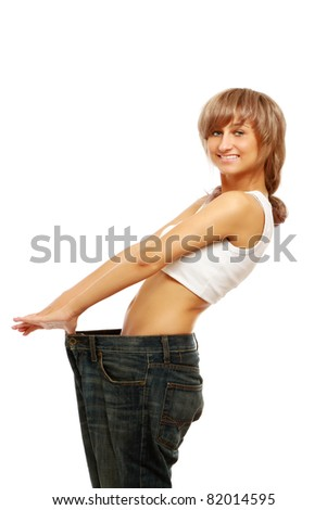 A smiling woman showing how much weight she lost, over white