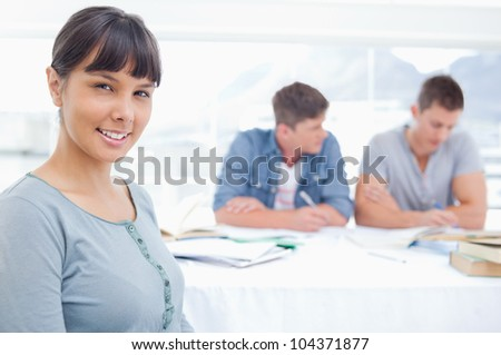 A smiling woman sits looking at the camera while her friends study in the background