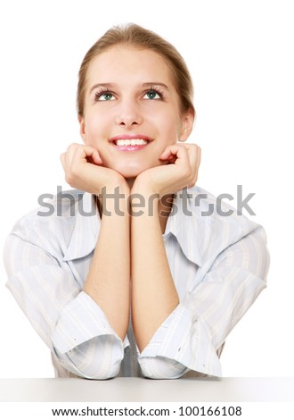 A smiling woman sitting at the desk and looking up , isolated on white