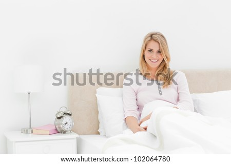 A smiling woman sitting upright while leaning back against the headboard. The alarm clock on the desk beside her showing the time.