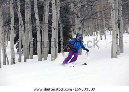 A smiling woman skiing in an aspen glade, Utah, USA.