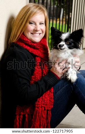 a smiling woman wearing a red scarf with a papillon dog.