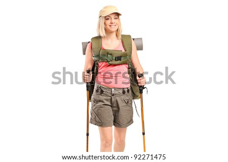 A smiling woman with backpack and hiking poles posing isolated on white background