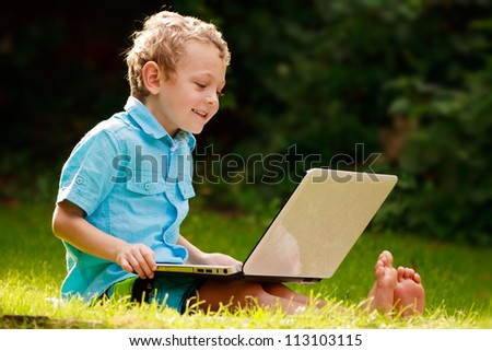 a smiling 5 year old boy sitting on the grass using a laptop