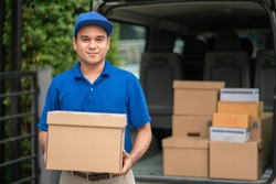 A smiling young asian delivery in blue uniform with parcel cardboard in front of customer house. Messenger and delivery concept.