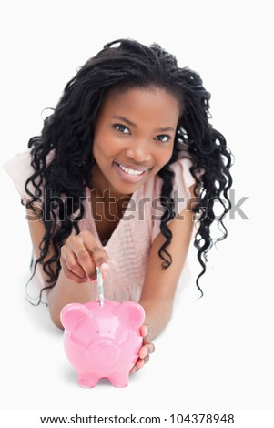 A smiling young girl is looking at the camera and putting money into a piggy bank against a white background