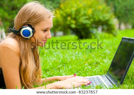 A smiling young girl with laptop outdoors listening music by headphones