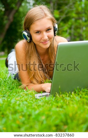 A smiling young girl with laptop outdoors listening music by headphones - stock photo