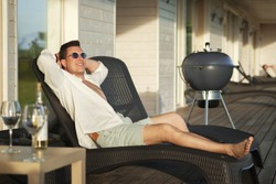 A smiling young man in sunglasses and a white shirt lies on a chaise longue on the wooden terrace.In front of him is a bottle of white wine and two glasses. A charcoal grill stands in the background.