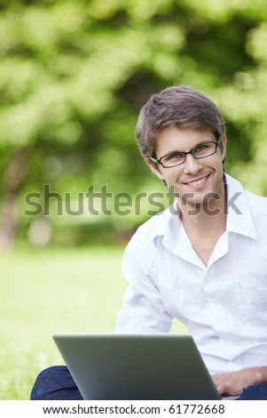A smiling young man with laptop outdoor