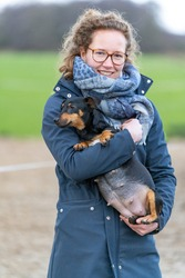 A smiling young woman holds a pregnant Jack russel terier in her arms. The dog's big belly can be seen clearly. Outside in the winter. Selective focus on dog.