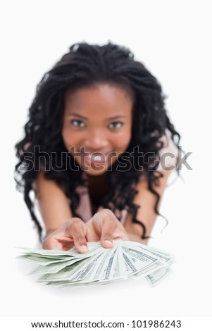 A smiling young woman is holding American dollars out in front of her against a white background