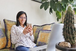 A smiling young woman relaxing in her living room after a work session, looking at her cell phone and wearing headphones