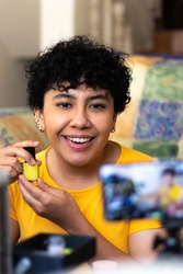 A smiling young woman, talking in front of a camera, showing a yellow nail polish, sitting on the floor of a living room on a sunny day