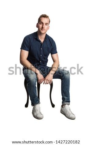 A smirking man sitting down on a stool in front of a white background, wearing a blue shirt and jeans with white shoes, looking at camera.
