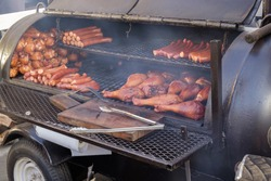 A Smoker Grill. A BBQ party with turkey legs and pork sausage. A great way to start that tailgating party