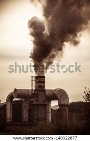 a smokestack erupting toxic fumes in the atmosphere
