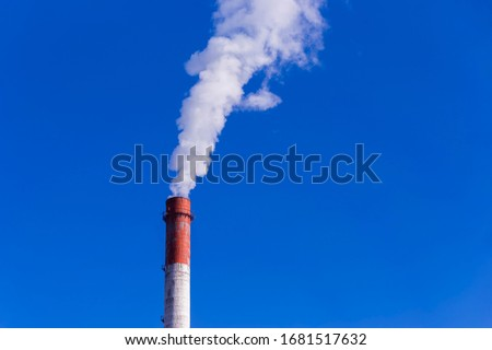 A smoking chimney in a blue sky. The emission of harmful gases into the atmosphere, greenhouse efekt. Air pollution, Closeup of one big smoking pipe. Zdjęcia stock ©