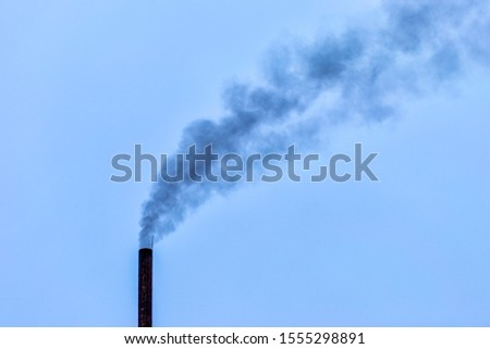 A smoking chimney with coal smoke in a blue sky. The emission of harmful gases into the atmosphere, greenhouse efekt. Air pollution, Closeup of one big smoking pipe. Zdjęcia stock ©