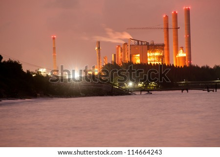 A smoking industrial power plant on seaside at night