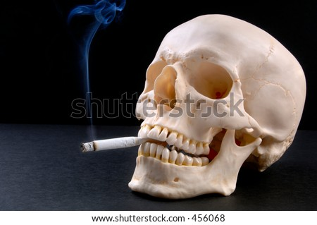 A smoking skull (12MP camera).  The skull is anatomically correct (medical model). The lighted cigarette has a smoke trail.