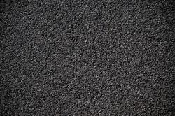 A smooth dark grey asphalt pavement texture with small rocks