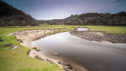 A smooth flowing river, located in Three Cliffs Bay, Wales, with Pennard Castle overlooking it from a distant hill