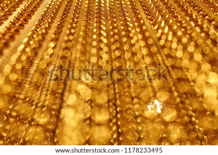A smooth movement of long gold chains. Uniform swing. Gold background for relaxation. Meditation. Relax. Texture for soothing. Glitter. View from bottom to top. Blurred