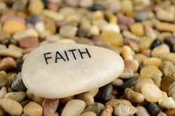 A smooth river stone is etched with the word faith for spiritual affirmation purposes.