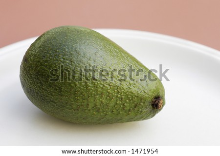 A smooth skinned avocado on a cream colored plate