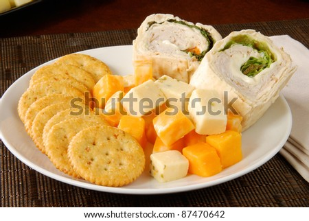 A snack plate with crackers, cheese and turkey wraps