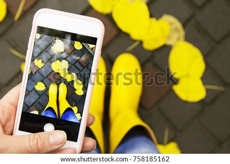 A snapshot of autumn on a smartphone. Bright yellow boots in foliage