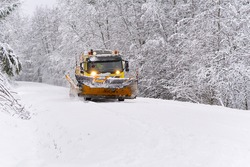 A snow blower car clears snow in the forest from the road on a winter morning. Snow plow truck cleaning icy white road