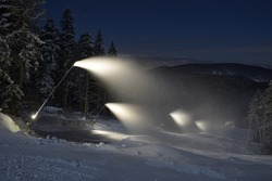 A snow cannon making snow in the winter at night