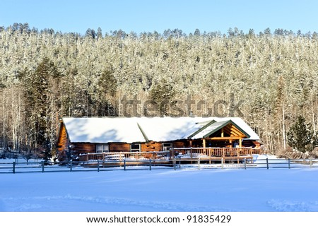 A snow capped mountain cabin resort surrounded by snow-covered trees