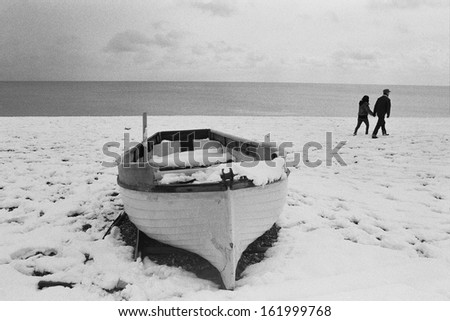 A snow-covered beach with a boat, and a couple walking past holding hands