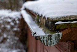 A snow-covered gutter on the roof. Snow lying on the roof and gutter for drainage. Winter season